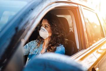 Young woman driving car with protective mask on her face.  Healthcare, virus protection, allergy protection concept. Fototapete