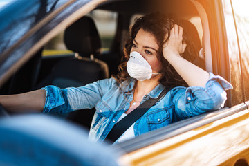Young woman driving car with protective mask on her face.  Healthcare, virus protection, allergy protection concept. Wall mural