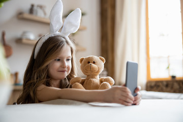 Funny child with her gadget and toy stock photo Fotobehang