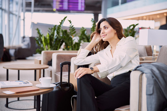 Beautiful lady waiting for flight in airport waiting room