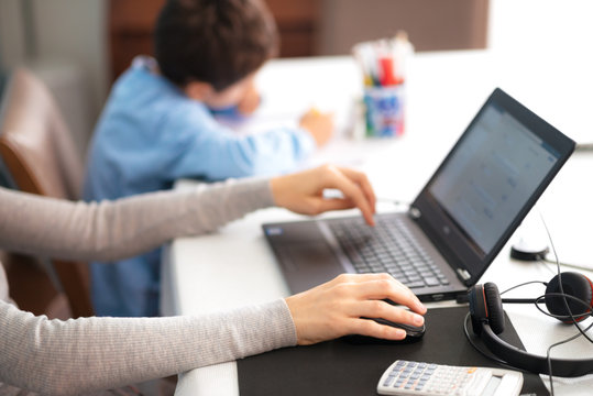 mother at home, smart working with laptop and headphones, while child is drawing