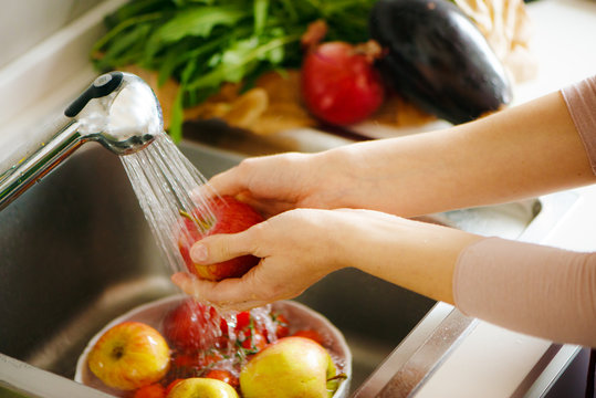 Washing fruit in the kitchen, white hands