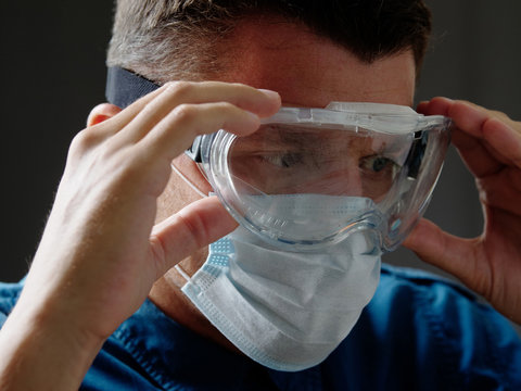 Portrait of a man in a medical mask puts on eye protection goggles.