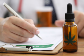 Closeup doctors hand writing prescription for hemp. Doctors prescribe cannabis for sleep...