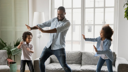 Photo on textile frame Dance School Happy African ethnicity father have fun teaches little preschool kids to dance in modern living room at home. Dad with son and daughter engaged in funny activity enjoy leisure carefree weekend concept