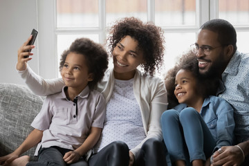 African ethnicity full family enjoy free time together relaxing on couch using smart phone new cool app, taking selfie picture capture moment or having distant communication making video call concept
