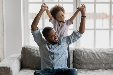 African loving father sitting on couch playing with little son holding hands enjoy funny activities on weekend at home. Concept of carefree free time together, having fun, love bond protection of kid