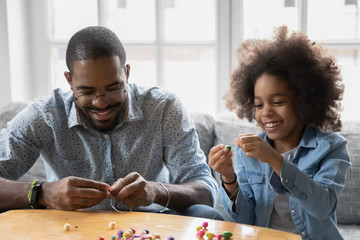 African dad and little daughter sit on couch use colorful beads making bracelet jewellery enjoy pastime together at home activity promote development, fine hand motor skills, pastime and hobby concept Wall mural