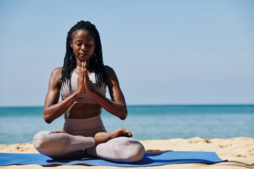 Beautiful slim young woman meditating in lotus position on the beach