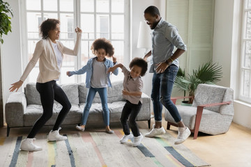 Full length view African ethnicity family dancing together in living room at new first home, young couple and little kids having fun listening music enjoy life cool weekends free time activity concept Fotobehang