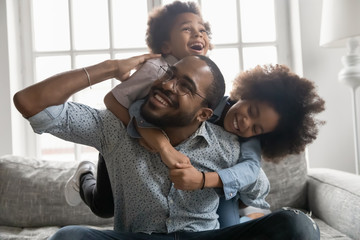 Happy African family at home, cute son and daughter hanging on daddy back, father fool around with...