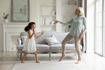 Cute little preschooler girl dancing entertaining with overjoyed active elderly grandmother at home, happy mature grandparent relax with small granddaughter, enjoy family weekend together