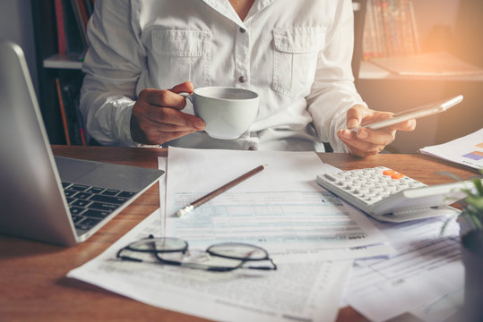Budget planning concept, Accountant is calculating company's annual tax. Calendar and personal income tax forms for those who have income under US law placed on office desk, working online at home