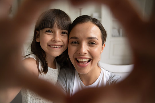 Close up portrait of little girl and young mom or nanny have fun make selfie with heart hand gesture, smiling mother play with small preschooler daughter take self-portrait picture at home together