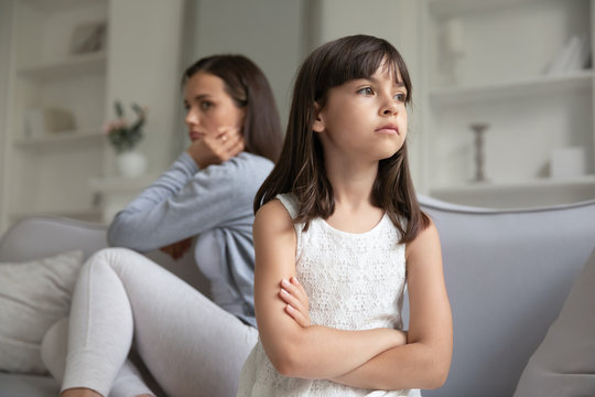 Offended young mother and little preschooler daughter sit separately ignore talking after fight, mad mom and small girl child avoid communication, have family misunderstanding, generation gap concept