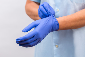Coronavirus prevention. The doctor puts on gloves to protect against coronavirus and germs.