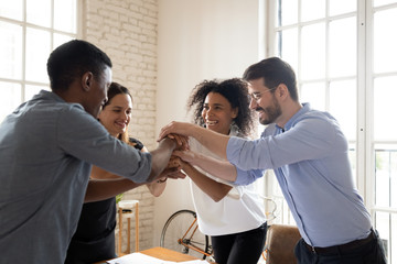 Four millennial different ethnicity teammates stacked palms together feels unity and support. Celebrating profitable deal, common success, leadership in market, participating in team building concept