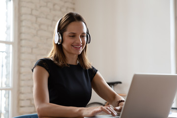 Smiling woman wearing wireless headphones working typing on notebook sit at desk in office workplace. Enjoy e-learning process, easy comfortable application usage, listen music during workday concept