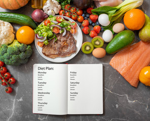 Foto op Canvas Kruidenierswinkel Journal with meal planning notes on a kitchen table surrounded by healthy products