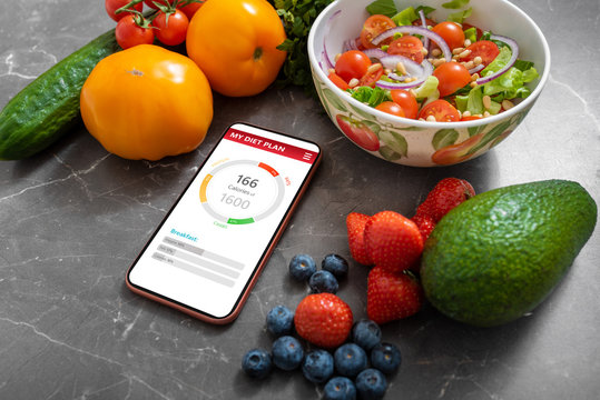 Smartphone with healthy meal planning app on a kitchen counter surrounded by vegetables and fruits