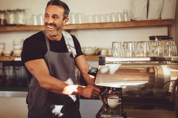 Smiling barista making espresso with a coffee maker Wall mural