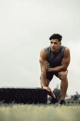 Muscular man taking break from cross training
