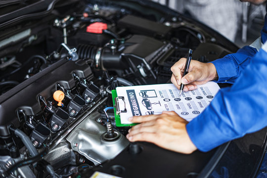 concept of a male asian engineer or a car mechanic looking inside car engine, holding a document on a clipboard diagnosing and checking parts to repair the car engine, wearing overall garnet and hat