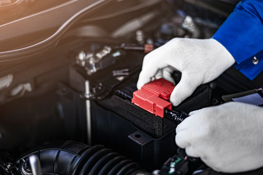 close up concept of male asian car mechanic repairing car battery positive terminal, representing business of car cleaning and maintenance service, wearing a white glove with car engine part checkups