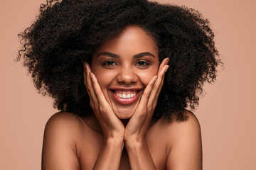 Positive African American woman with healthy skin looking at camera