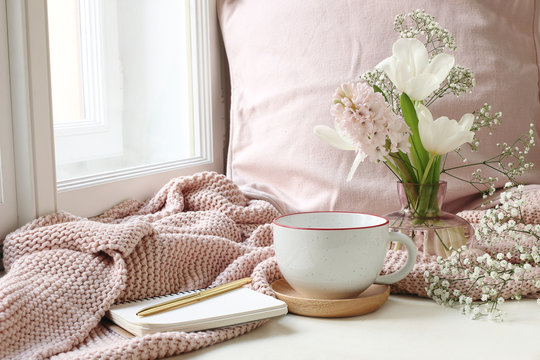 Cozy Easter, spring still life scene. Cup of coffee, notebook, golden pen, pink knitted plaid near window. Vintage feminine styled photo. Floral composition with tulips, hyacinth and Gypsophila