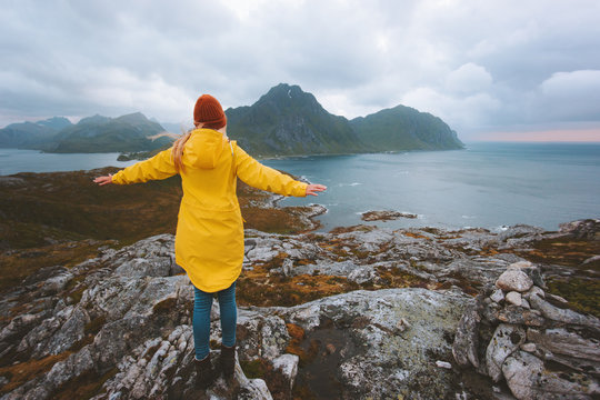 Woman traveler raised hands enjoying rainy mountains view traveling in Norway alone active vacations healthy lifestyle outdoor Lofoten islands landscape