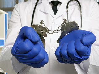 Medical negligence or neglect concept. Doctor stands in handcuffs. Wall mural