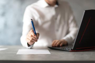 Obraz Pracownik w białej koszuli zachęca do podpisania dokumenu, umowy. Długopis w dłoni. Biznesmen przy laptopie w biurze. - fototapety do salonu