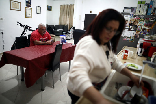 Palestinian man Victor Anton Sara, 41, uses his mobile phone as his wife Jizelle, 42, cleans dishes as they spend time together while observing a partial lockdown to curb the spread of the coronavirus disease (COVID-19) at their home in Jerusalem