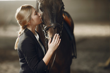 Woman near horse. Rider in a black uniform
