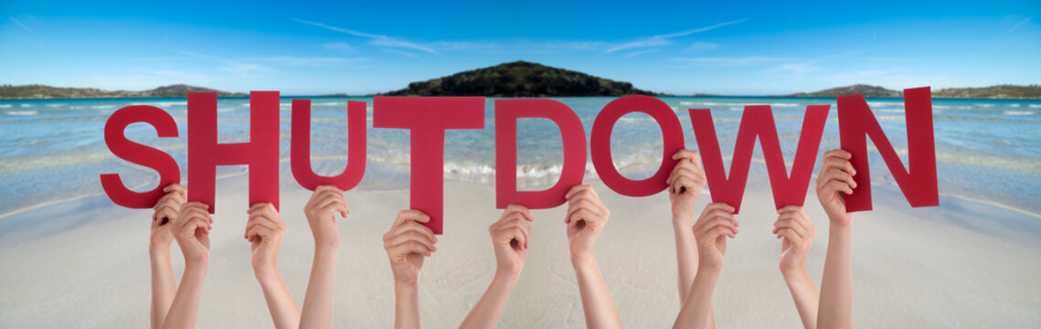 People Hands Holding Colorful English Word Shutdown. Ocean And Beach As Background