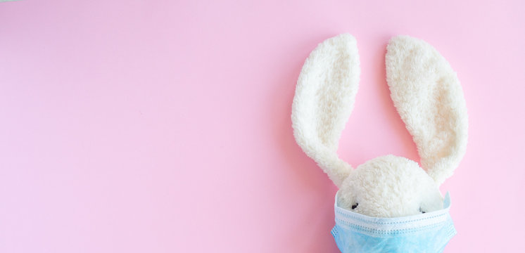 Easter quarantine concept, flat lay white bunny rabbit with face  protective mask on pink background. Copy space, top view.