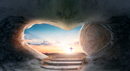Easter concept: Empty Tomb Of Jesus Christ At Sunrise With Cross background
