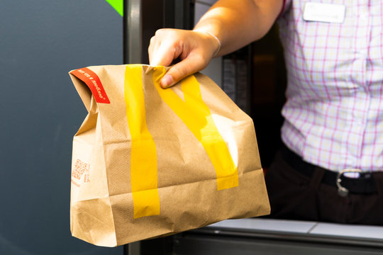Sankt-Petersburg/Russia - July 21 2019: McDonald's worker holding bag of fast food. Hand with a paper bag through the window of mcdonalds car drive thru service.