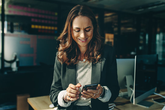Woman entrepreneur using a phone in office