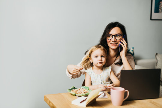 Woman works at home on a laptop with a child. Mom works remotely at home. Lifestyle photos.