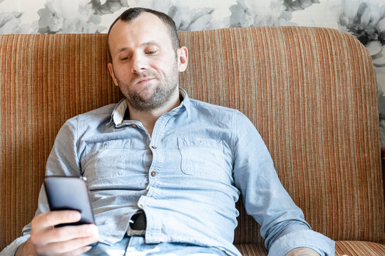 bored young man looking at smartphone during home isolation during pandemic coronovirus covid -19