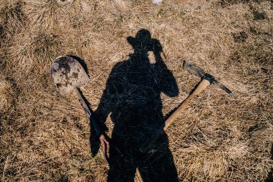 Schatten eines Mannes mit Hut, Spitzhacke und Spaten