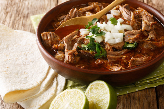 Mexican style slow cooked beef stew Birria de Res served with lime and tortilla closeup in a bowl. horizontal