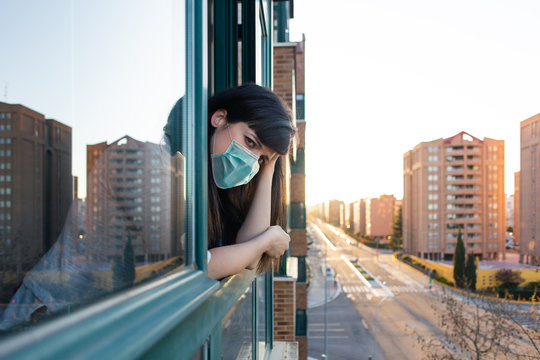 Bored woman with ffp2 face mask peeks out the window during quarantine over covid-19 crisis. Stay at home concept. Empty city under confinement. Valladolid, Spain.