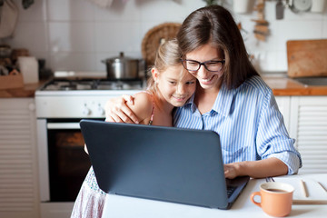 Working from home office with kid. Happy mother and daughter shopping online, using laptop together. Woman hugging child. Freelancer workplace at kitchen table. Female business, virtual communication.