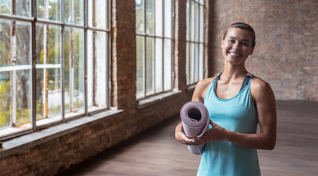 Happy attractive sporty fit young woman yoga class training instructor personal fitness trainer wear sportswear holding rolled yoga mat standing in gym looking at camera, portrait banner copy space