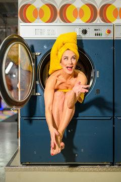frau sitzt nur mit handtuch bekleidet in großer waschmaschiene