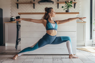 Young fit woman exercising at home doing warrior pose.
