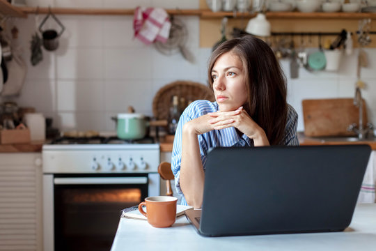 Working from home office. Upset woman using laptop and Internet. Freelancer workplace at kitchen table. Remote female business and career, stress in social distancing, self-isolation. Lifestyle moment